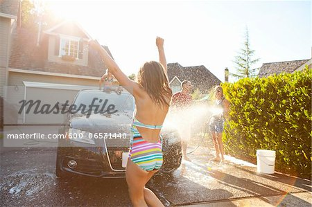 Young girl dances while family washes their car in the driveway of their home on a sunny summer afternoon in Portland, Oregon, USA Stock Photo - Premium Royalty-Free, Image code: 600-06531440