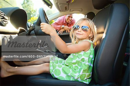 Portrait of little girl sitting in driver's seat of car, pretending to be old enough to drive as her smiling father watches on on a sunny summer evening in Portland, Oregon, USA Stock Photo - Premium Royalty-Free, Image code: 600-06531449