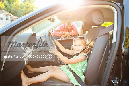 Little girl sitting in driver's seat of car wearing seatbelt, pretending to be old enough to drive and showing she knows the importance of a seat belt as her smiling father watches on on a sunny summer evening in Portland, Oregon, USA Stock Photo - Premium Royalty-Free, Image code: 600-06531450