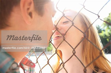 Young couple kissing through chain link fence in park near the tennis court on a warm summer day in Portland, Oregon, USA Stock Photo - Premium Royalty-Free, Image code: 600-06531460