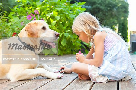 Little girl painting the claws of a dog with bright pink nail polish on a sunny summer afternoon in Portland, Oregon, USA Stock Photo - Premium Royalty-Free, Image code: 600-06531467