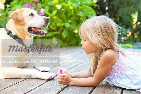 Little girl painting the claws of a dog with bright pink nail polish on a sunny summer afternoon in Portland, Oregon, USA Stock Photo - Premium Royalty-Free, Image code: 600-06531468