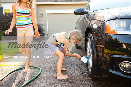 Sisters washing car in the driveway of their home on a sunny summer afternoon in Portland, Oregon, USA Stock Photo - Premium Royalty-Free, Image code: 600-06531471