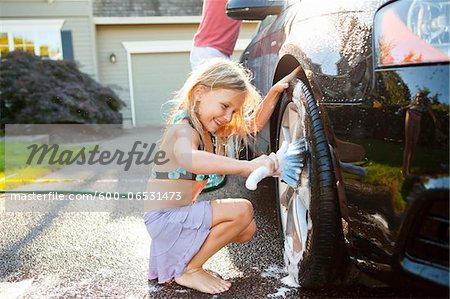 Young daughter helps father wash their car in the driveway of their home on a sunny summer afternoon in Portland, Oregon, USA Stock Photo - Premium Royalty-Free, Image code: 600-06531473