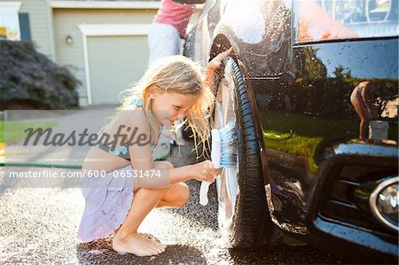 Young daughters help father wash their car in the driveway of their home on a sunny summer afternoon in Portland, Oregon, USA Stock Photo - Premium Royalty-Free, Image code: 600-06531474