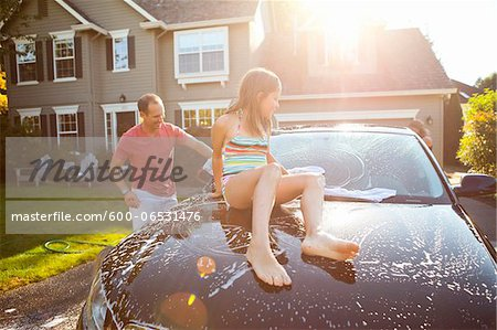 Family washing their car in the driveway of their home on a sunny summer afternoon in Portland, Oregon, USA Stock Photo - Premium Royalty-Free, Image code: 600-06531476