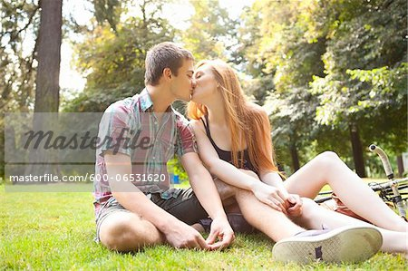 Young Couple Sitting on the Ground and Kissing in Park on a Summer Day, Portland, Oregon, USA Stock Photo - Premium Royalty-Free, Image code: 600-06531620