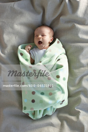 newborn baby girl in a white undershirt yawning on a bed swaddled in a baby blanket Stock Photo - Premium Royalty-Free, Image code: 600-06531991