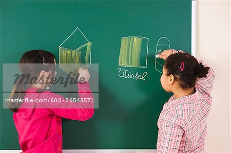 Girls Drawing on Blackboard in Classroom, Baden-Wurttemberg, Germany Stock Photo - Premium Royalty-Free, Image code: 600-06548571