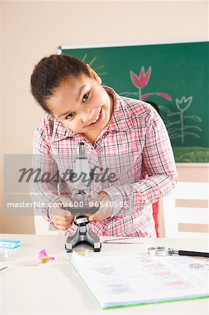 Girl Looking at Flower with Microscope in Classroom, Baden-Wurttemberg, Germany Stock Photo - Premium Royalty-Free, Image code: 600-06548585