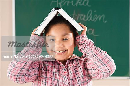 Girl With Textbook on her Head in Classroom, Baden-Wurttemberg, Germany Stock Photo - Premium Royalty-Free, Image code: 600-06548599