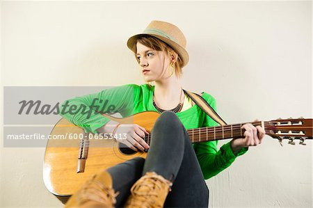 Portrait of Teenage Girl Wearing Hat and Playing Acoustic Guitar, Studio Shot on White Background Stock Photo - Premium Royalty-Free, Image code: 600-06553413
