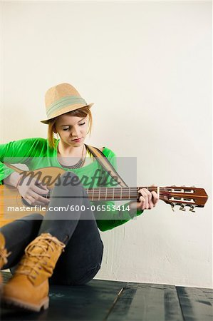 Portrait of Teenage Girl Sitting on Floor, Wearing Hat and Playing Acoustic Guitar, Studio Shot on White Background Stock Photo - Premium Royalty-Free, Image code: 600-06553414