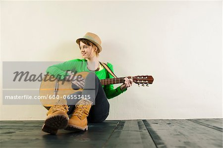 Portrait of Teenage Girl Sitting on Floor, Wearing Hat and Playing Acoustic Guitar, Studio Shot on White Background Stock Photo - Premium Royalty-Free, Image code: 600-06553415