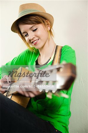 Portrait of Teenage Girl Wearing Hat and Playing Acoustic Guitar, Studio Shot on White Background Stock Photo - Premium Royalty-Free, Image code: 600-06553416