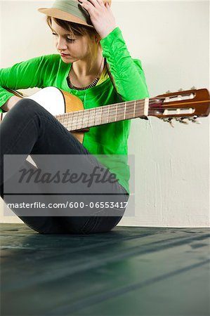 Portrait of Teenage Girl Sitting on Floor, Wearing Hat and holding Acoustic Guitar, Studio Shot on White Background Stock Photo - Premium Royalty-Free, Image code: 600-06553417