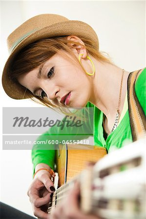 Close-up Portrait of Teenage Girl Wearing Hat and Playing Acoustic Guitar, Studio Shot on White Background Stock Photo - Premium Royalty-Free, Image code: 600-06553418