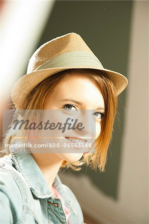 Head and shoulders portrait of teenage girl wearing hat in studio. Stock Photo - Premium Royalty-Free, Image code: 600-06553548