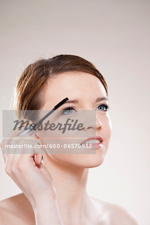 Head and Shoulders Portrait of Teenage Girl Putting on Mascara in Studio Stock Photo - Premium Royalty-Free, Image code: 600-06570932
