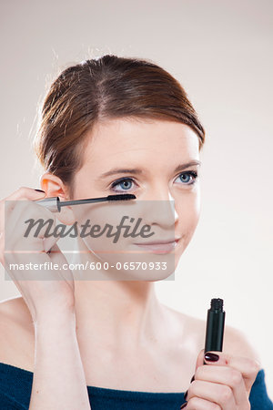 Head and Shoulders Portrait of Teenage Girl Putting on Mascara in Studio Stock Photo - Premium Royalty-Free, Image code: 600-06570933