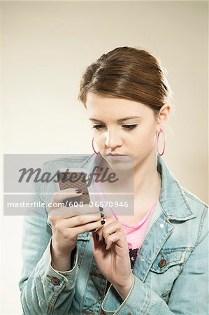 Portrait of Teenage Girl Reading Text Message on a Cell Phone in Studio Stock Photo - Premium Royalty-Free, Image code: 600-06570946