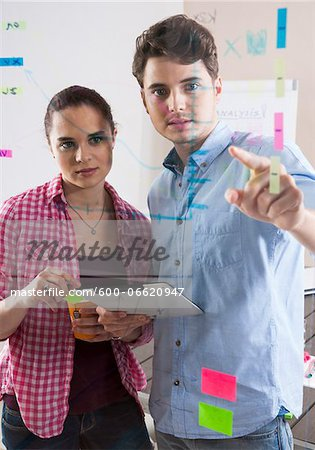 Young Man and Young Woman Working in an Office, Looking Through Glass Board, Germany Stock Photo - Premium Royalty-Free, Image code: 600-06620947