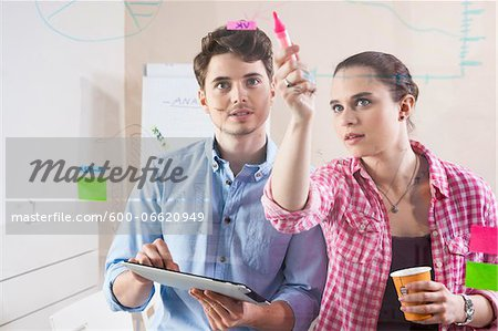 Young Man and Young Woman Working in an Office, Looking Through Glass Board, Germany Stock Photo - Premium Royalty-Free, Image code: 600-06620949