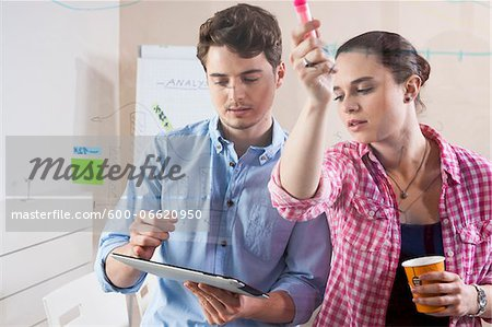 Young Man and Young Woman Working in an Office, Looking Through Glass Board, Germany Stock Photo - Premium Royalty-Free, Image code: 600-06620950