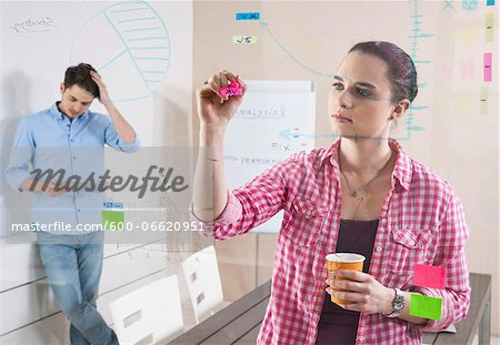 Young Man and Young Woman Working in an Office, Looking Through Glass Board, Germany Stock Photo - Premium Royalty-Free, Image code: 600-06620951