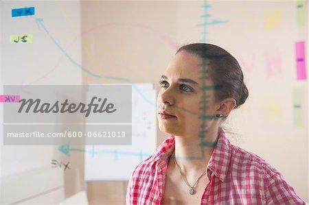 Young Businesswoman Working in Office Looking at Plans Displayed on a Glass Board Stock Photo - Premium Royalty-Free, Image code: 600-06621019