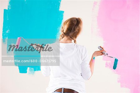 Studio Shot of Young Woman Holding Paint Rollers, Deciding Between Paint Colours
