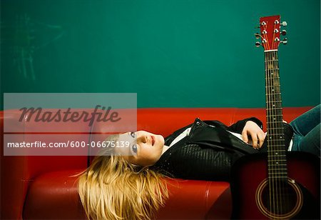 Woman Lying on Sofa with Acoustic Guitar Stock Photo - Premium Royalty-Free, Image code: 600-06675139