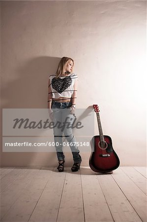 Woman Wrapped in Microphone Cord beside Acoustic Guitar Stock Photo - Premium Royalty-Free, Image code: 600-06675148