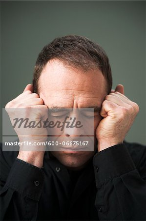Head and Shoulders Portrait of Mature Man Eyes Closed and Fists by Head Stock Photo - Premium Royalty-Free, Image code: 600-06675167