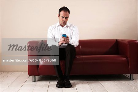 Mature Man Sitting on Sofa, Waiting and Looking at Cell Phone Stock Photo - Premium Royalty-Free, Image code: 600-06679368