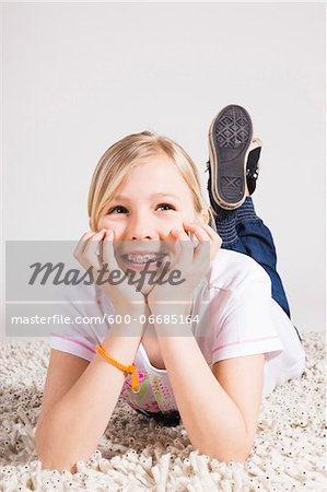 Portrait of Girl Leaning on Hands and Lying on Stomach in Studio Stock Photo - Premium Royalty-Free, Image code: 600-06685164