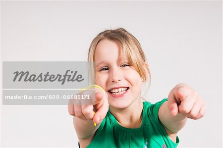Head and Shoulders Portrait of Girl Pointing at Camera in Studio Stock Photo - Premium Royalty-Free, Image code: 600-06685171