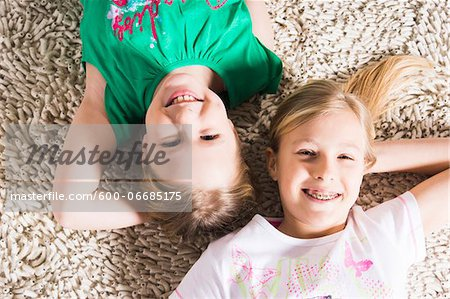 Overhead View of Girls lying on Carpet in Studio Stock Photo - Premium Royalty-Free, Image code: 600-06685175