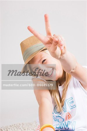 Portrait of Girl wearing Hat and making Peace Sign Gesture in Studio Stock Photo - Premium Royalty-Free, Image code: 600-06685179