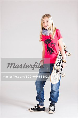 Full Length Portrait of Girl with Skateboard in Studio Stock Photo - Premium Royalty-Free, Image code: 600-06685182
