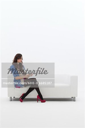 Young Businesswoman Sitting on Sofa using Tablet Computer, Studio Shot on White Background Stock Photo - Premium Royalty-Free, Image code: 600-06685187
