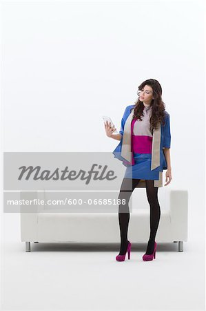 Young Businesswoman Standing in front of Sofa using Tablet Computer, Studio Shot on White Background Stock Photo - Premium Royalty-Free, Image code: 600-06685188