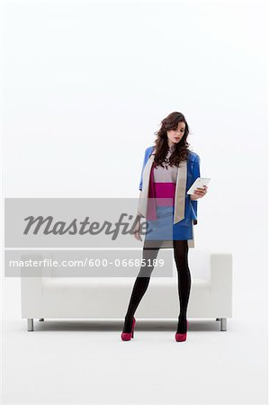 Young Businesswoman Standing in front of Sofa using Tablet Computer, Studio Shot on White Background Stock Photo - Premium Royalty-Free, Image code: 600-06685189