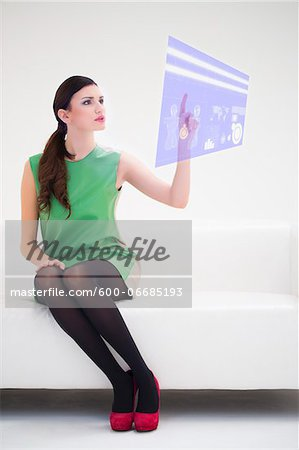 Young Businesswoman Sitting on Sofa using Digital Display, Studio Shot on White Background Stock Photo - Premium Royalty-Free, Image code: 600-06685193