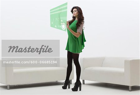 Young Businesswoman Standing in front of Sofa using Digital Display, Studio Shot on White Background Stock Photo - Premium Royalty-Free, Image code: 600-06685194