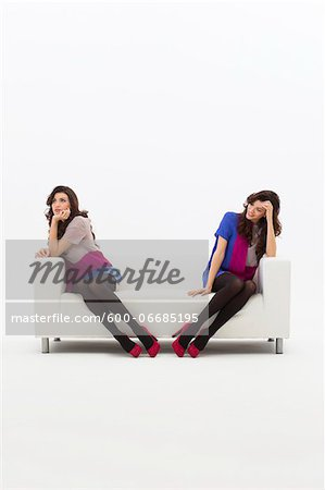 Multiple Image of Young Woman Sitting on Sofa, Studio Shot on White Background Stock Photo - Premium Royalty-Free, Image code: 600-06685195