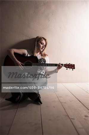 Young Woman Sitting on the Floor Playing Guitar in Studio Stock Photo - Premium Royalty-Free, Image code: 600-06701796