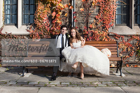 Portrait of Bride and Groom Sitting on Bench in Autumn, Toronto, Ontario, Canada Stock Photo - Premium Royalty-Free, Image code: 600-06701871