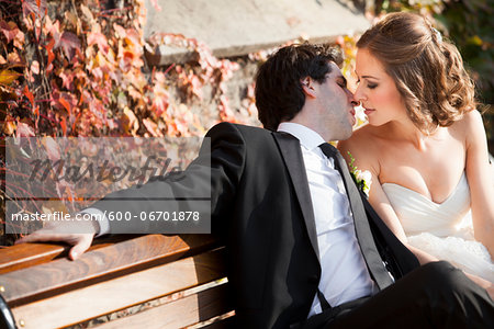 Portrait of Bride and Groom Kissing on Bench in Autumn, Toronto, Ontario, Canada Stock Photo - Premium Royalty-Free, Image code: 600-06701878