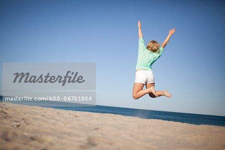 Back View of Young Woman Jumping on Beach, Palm Beach Gardens, Palm Beach County, Florida, USA Stock Photo - Premium Royalty-Free, Image code: 600-06701904